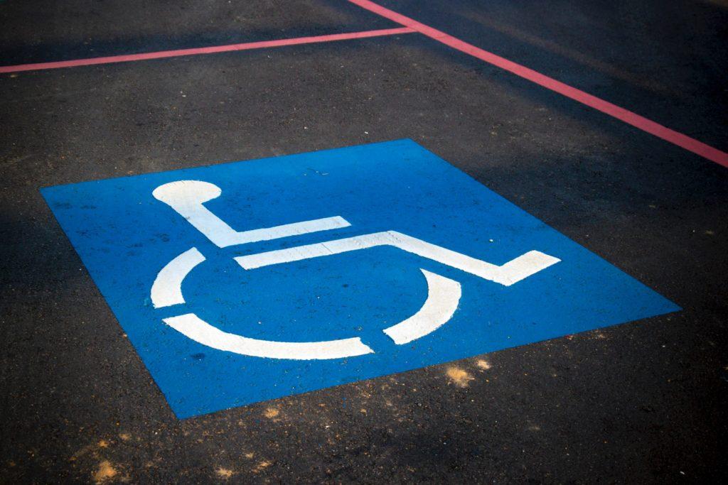 Na zdjęciu znajduje się znak osoby niepełnosprawnej na wózku. Jest to miejsce parkingowe. Symbol osób niepełnopsrawnych